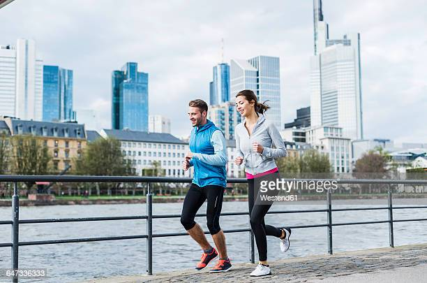 young couple running at the river