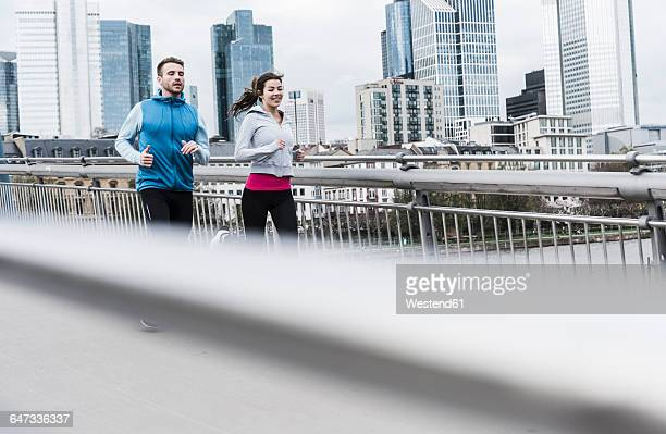 young couple running at the river - frankfurt main bildbanksfoton och bilder