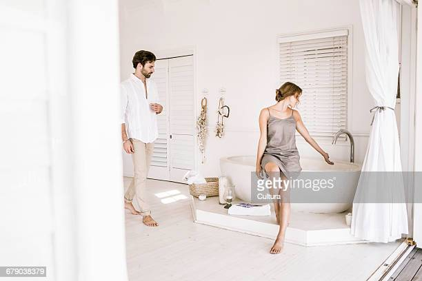 Young couple running bathtub water in morning