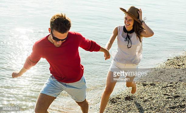 Young couple running hand in hand by the riverside