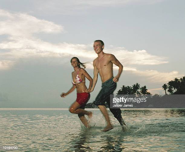 young couple running in surf, holding hands, thailand (blurred motion) - wading stock pictures, royalty-free photos & images