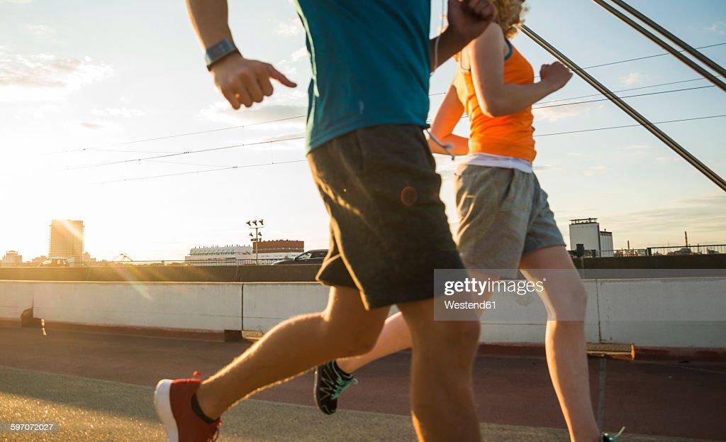 Young couple running on a bridge : ストックフォト