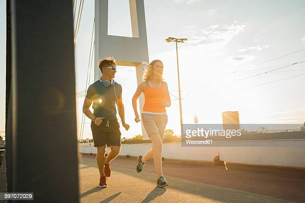 Young couple running on a bridge