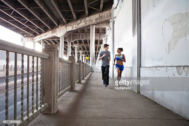young couple running on city bridge - heshphoto stockfoto's en -beelden