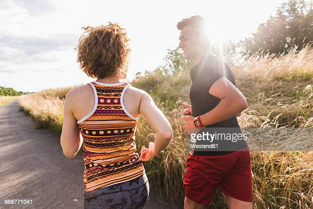 Young couple running on country lane