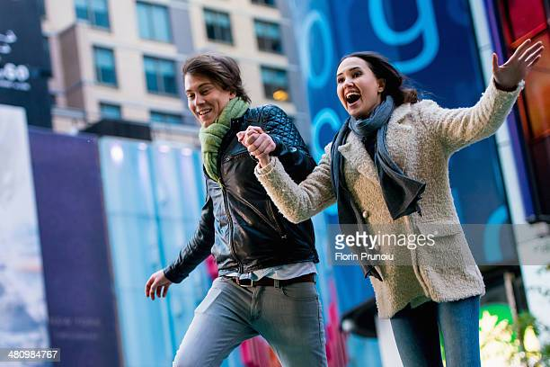 Young couple running on street, New York City, USA