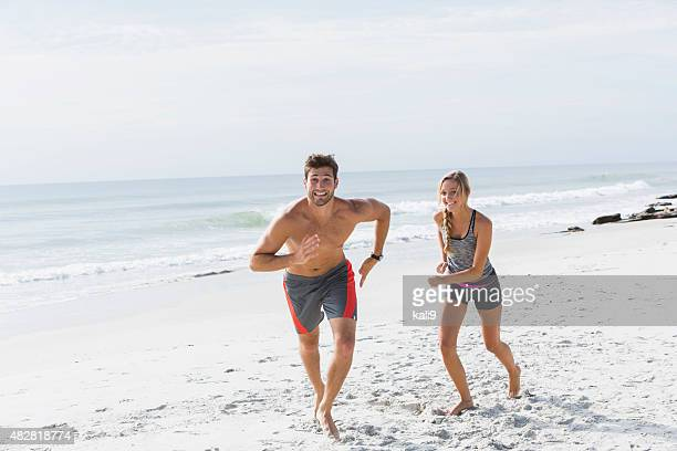 Young couple running on the beach, being playful