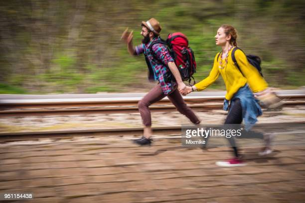Young couple running on the railway platform