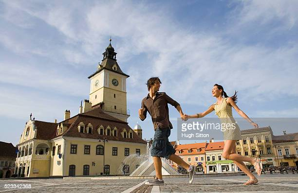 young couple running through public square - hugh sitton stock pictures, royalty-free photos & images