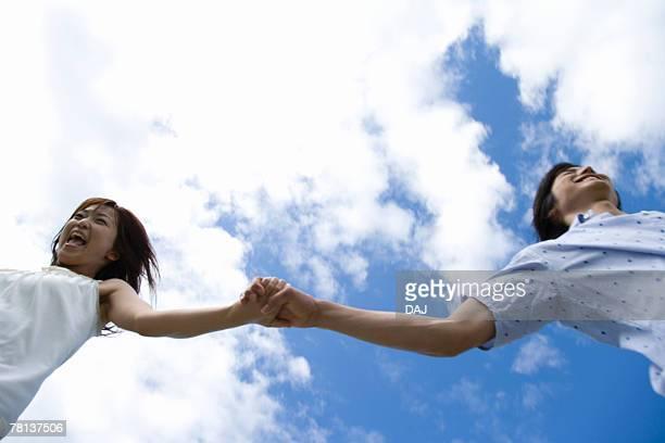 young couple running under the sky, hand in hand, saipan  - 北マリアナ諸島 ストックフォトと画像