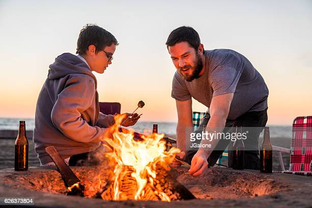Young couple sat around a camp fire making s'mores