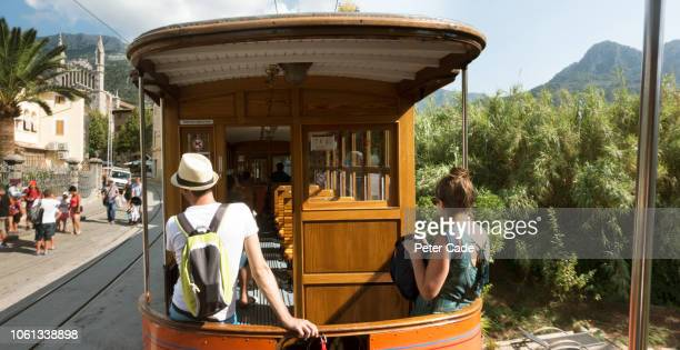 young couple sat at back of train going through town - palma majorca stock pictures, royalty-free photos & images