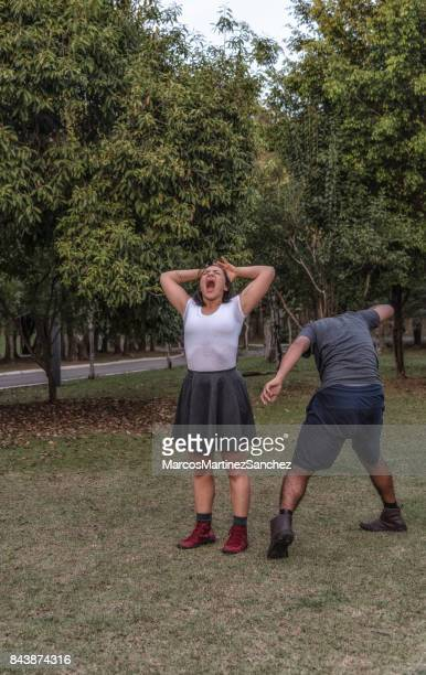 Young couple screaming and staging in park
