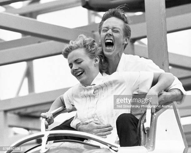 A young couple screams as their roller coaster car drops in San Francisco California
