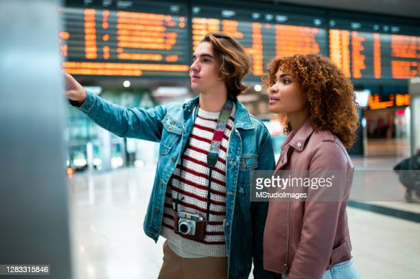 young couple searching for information about the departure of train - train vehicle stock pictures, royalty-free photos & images