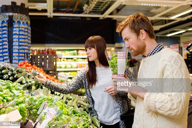 Young couple selecting vegetables at supermarket