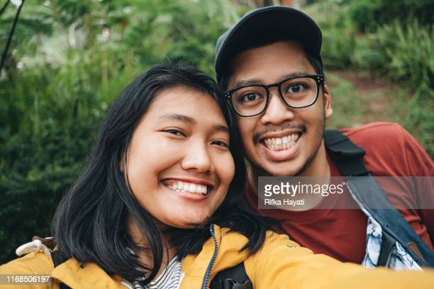 young couple selfie together while travelling in bandung - bandung stock pictures, royalty-free photos & images