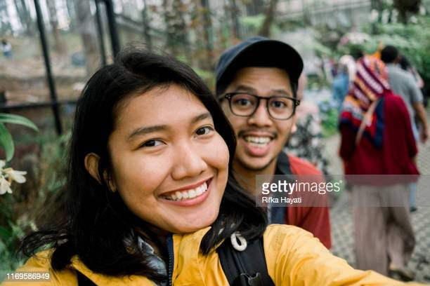 young couple selfie together while travelling in bandung - indonesian culture stock pictures, royalty-free photos & images