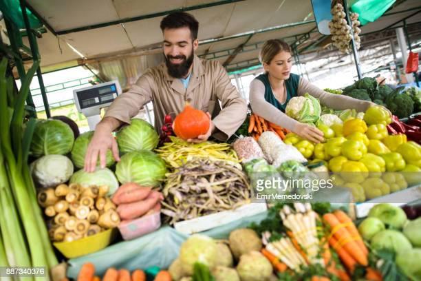 Pareja joven vendiendo verduras en la tienda del agricultor
