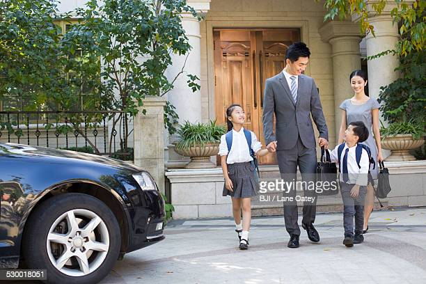 Young couple sending their children to school