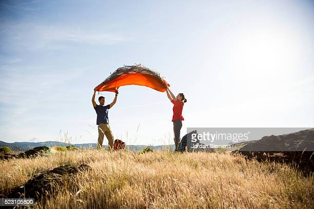 Young couple setting up tent in field, Oregon, USA