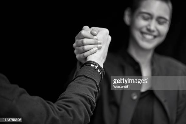 young couple shaking hands - consensus 2018 stock pictures, royalty-free photos & images