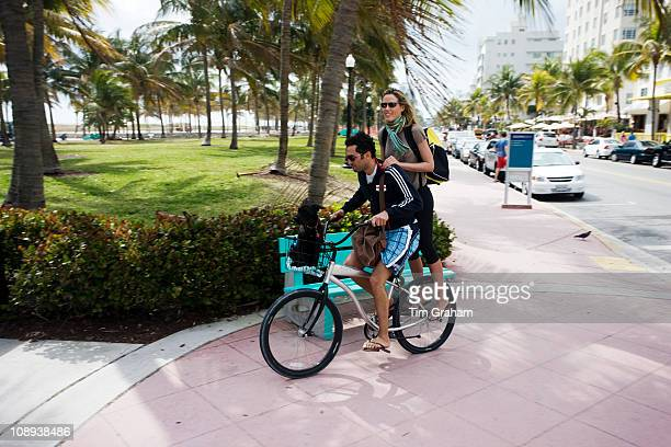 Young couple sharing a bicycle on Ocean Drive South Beach Miami Florida USA