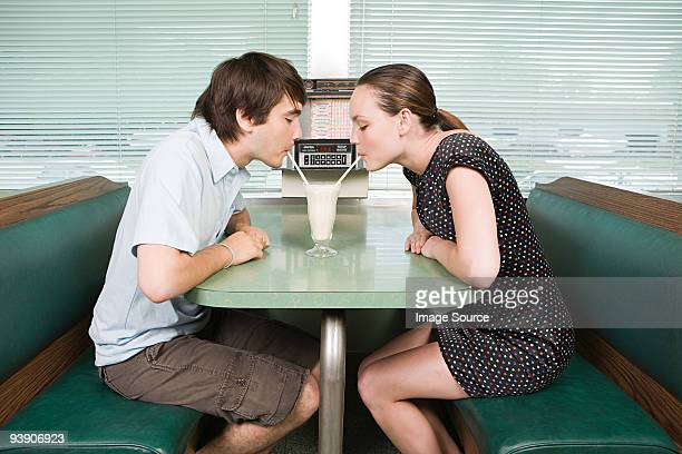 Young couple sharing a milkshake
