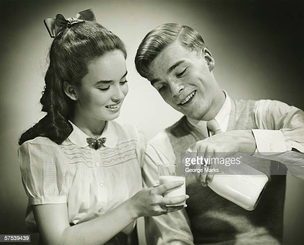 Young couple sharing bottle of milk, smiling, (B&W), close-up
