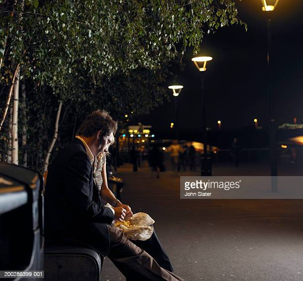 Young couple sharing chips on street bench, night, side view
