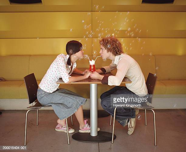 Young couple sharing drink, surrounded by bubbles