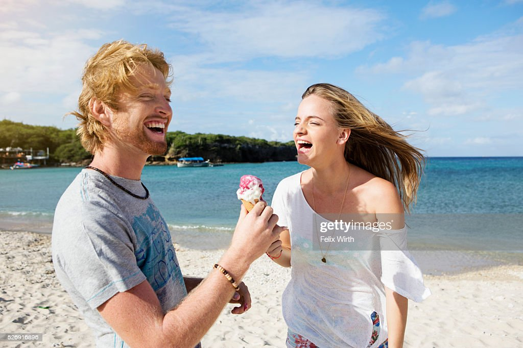 Young couple sharing ice cream at beach : ストックフォト