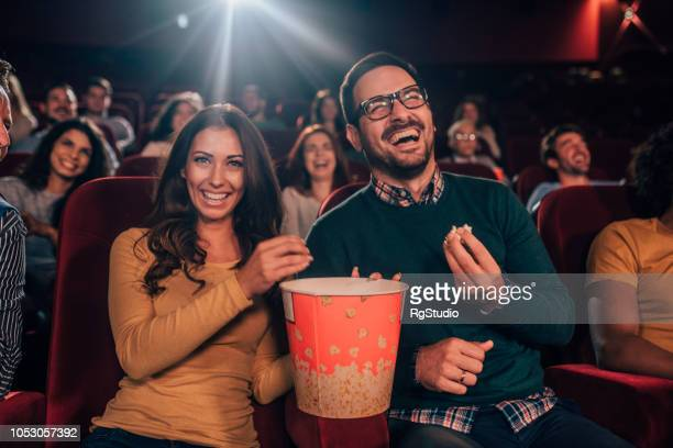 young couple sharing popcorn at cinema - comedy film stock photos and pictures