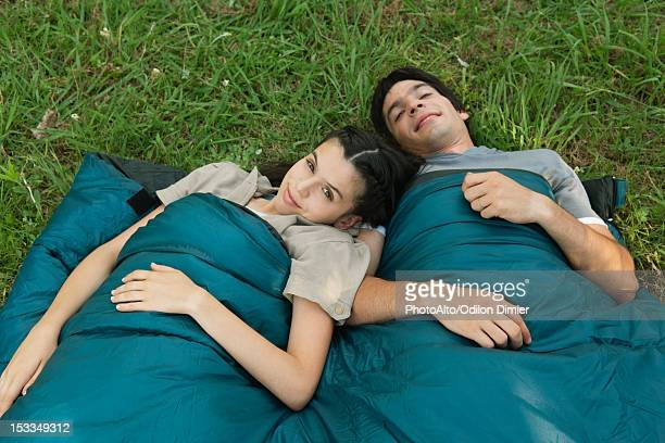 Young couple sharing sleeping bag in field