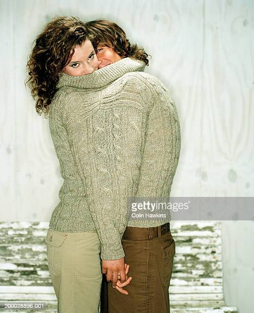 young couple sharing sweater, portrait - warm clothing stock pictures, royalty-free photos & images