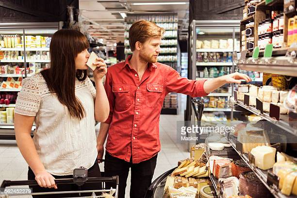 Young couple shopping cheese at supermarket