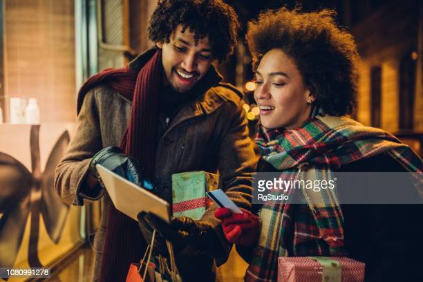 Young couple shopping for Christmas presents online