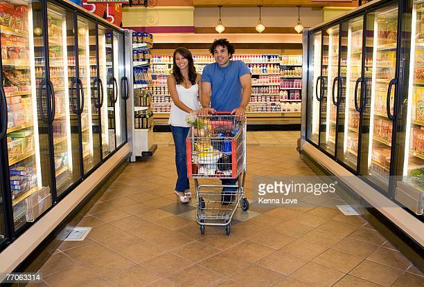 Young couple shopping in frozen food section of grocery store