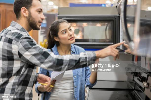 young couple shopping in home improvement warehouse - appliance stock pictures, royalty-free photos & images