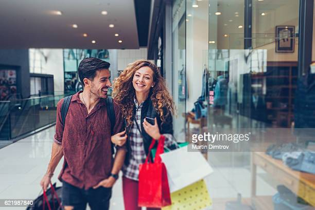 young couple shopping in the mall - winkelen stockfoto's en -beelden