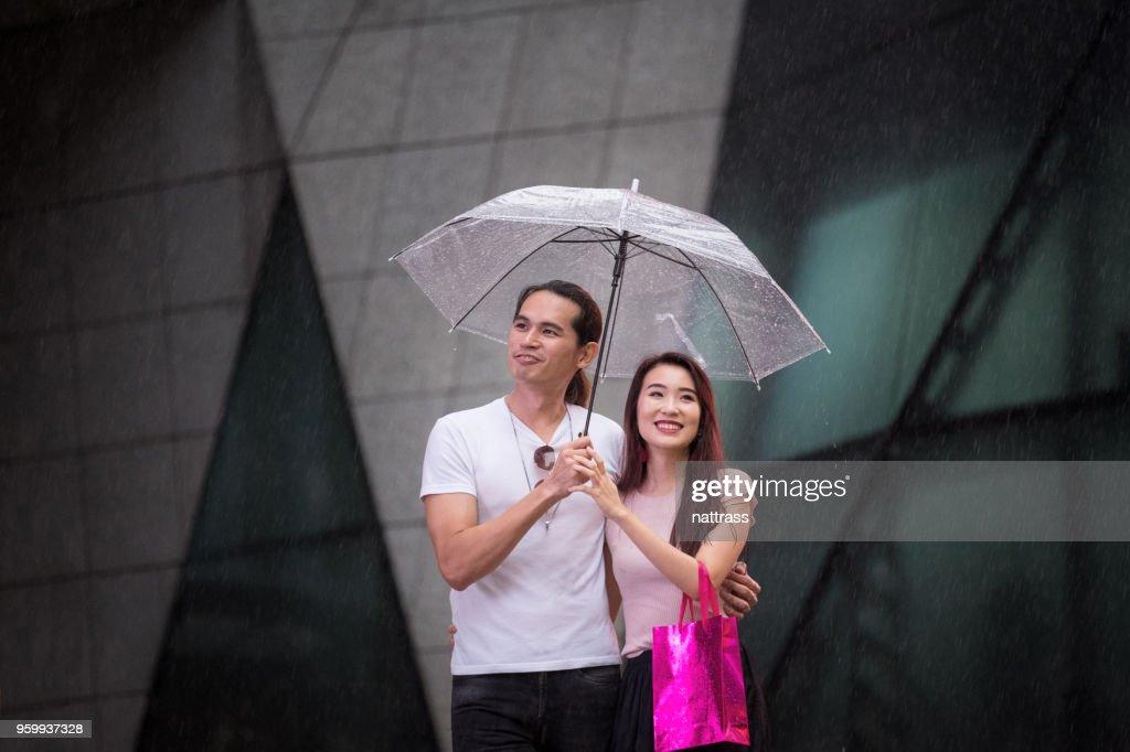 Junges paar Einkaufen im Regen : Stock-Foto