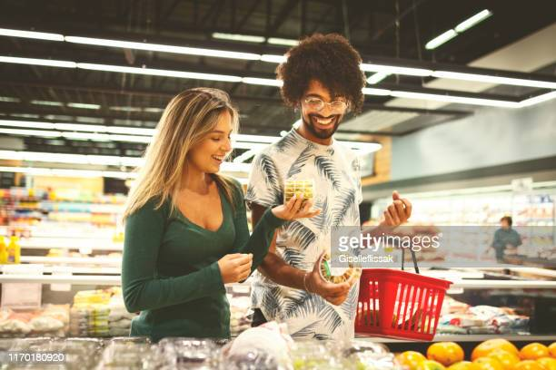 young couple shopping in the supermarket - ready to eat stock pictures, royalty-free photos & images