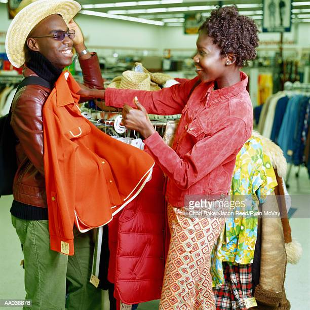 Young couple shopping in thrift store, man trying on hat, side view