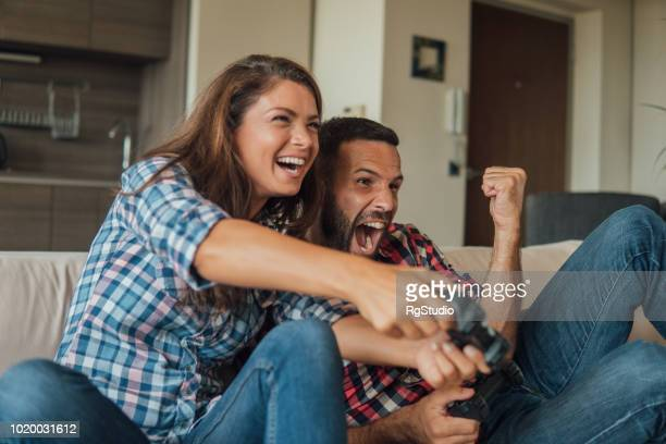 Young couple shouting in joy while playing video games
