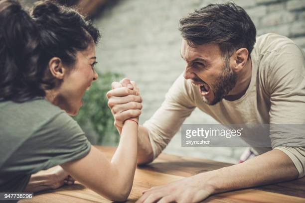 Young couple shouting while arm wrestling at home.