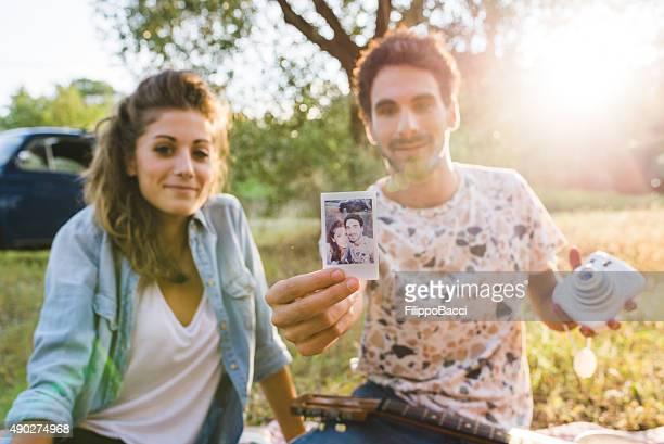 Young Couple Showing A Vintage Selfie Photo