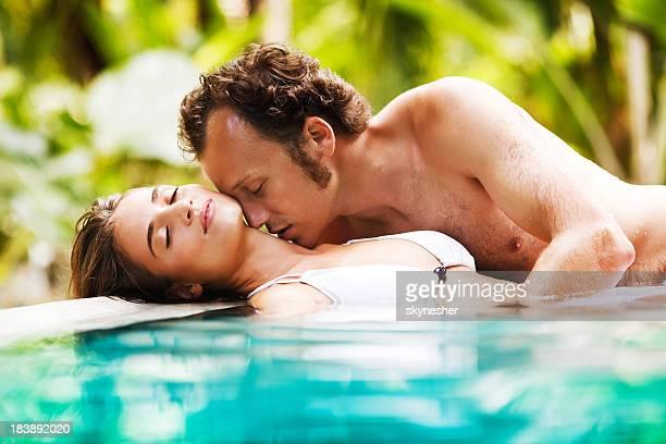 Junges Paar, die Zuneigung in einen tropischen pool in Thailand.