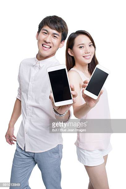 Young couple showing smart phones