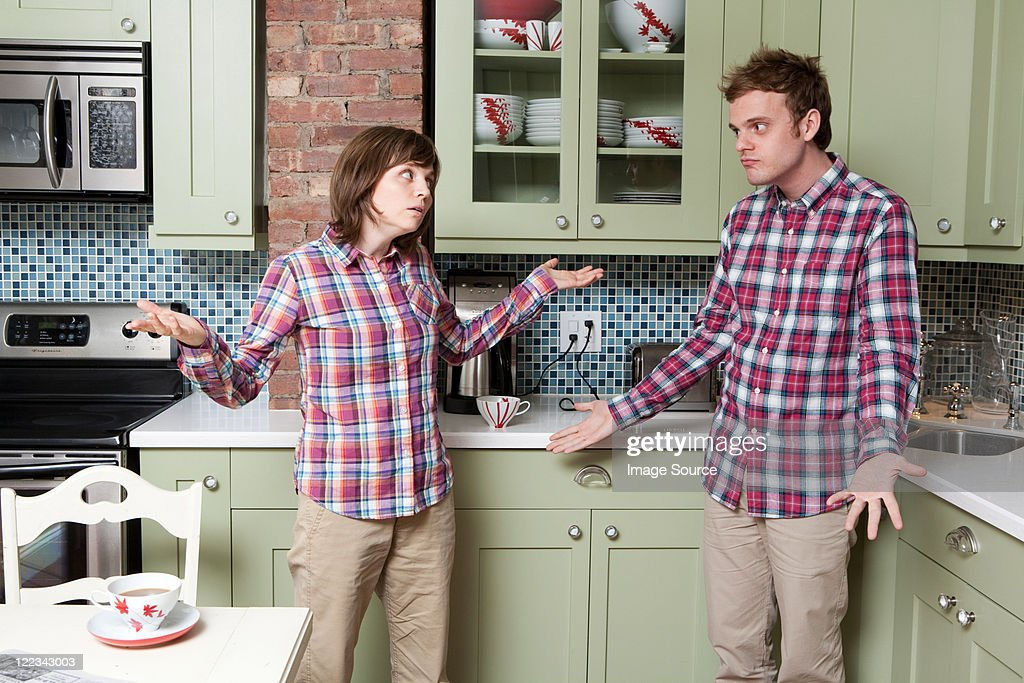 Young couple shrugging in kitchen : Stock Photo