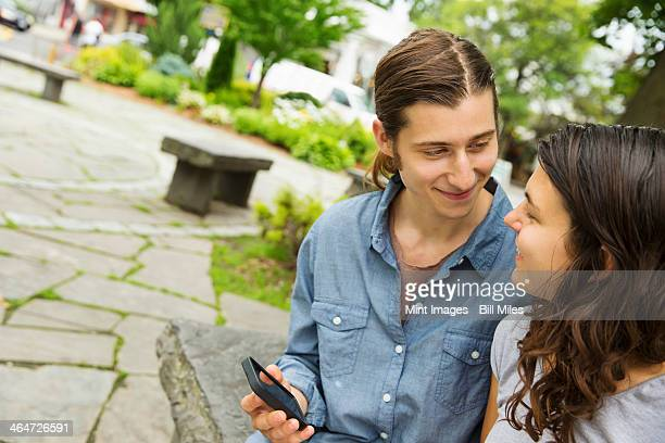 A young couple side by side,flirting and taking photographs.
